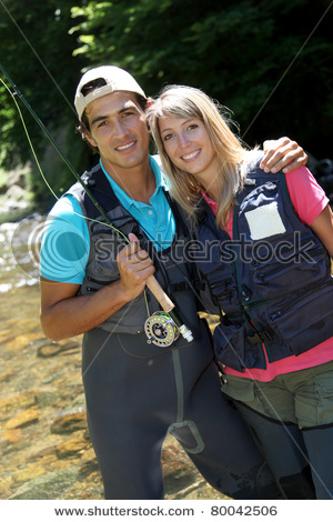 stock-photo-portrait-of-couple-fly-fishing-in-river-80042506